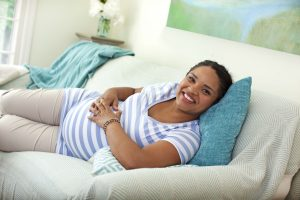 Smiling pregnant woman lying on couch